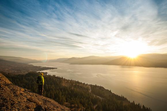 Hiker above Naramata and Okanagan Lake during sunset