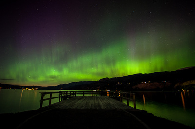 Green and purple northern lights fill the night sky over Naramata's Wharf Park and Okanagan Lake in the South Okanagan Valley, British Columbia.